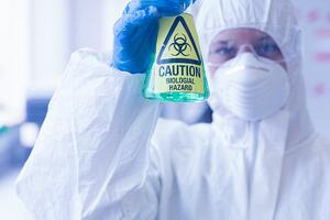 Close-up of a scientist in protective suit with hazardous blue chemical in flask at the laboratory-2