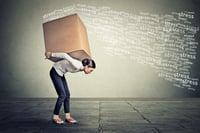 Zestresowana kobieta niosąca na plecach duże pudło.jpeg